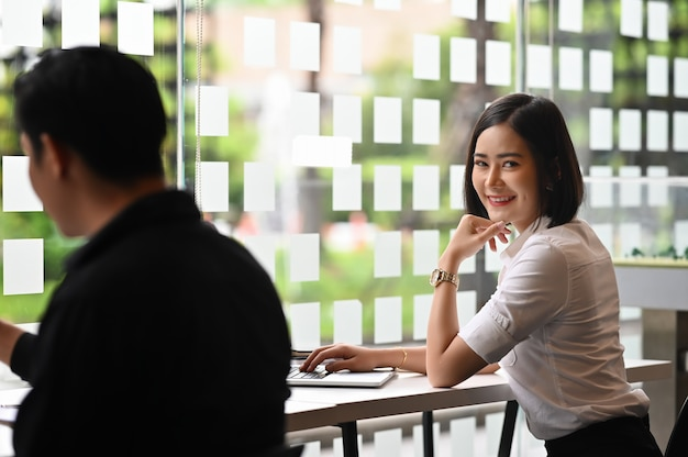 Female working on laptop in co working space with portrait shot looking at camera. Premium Photo