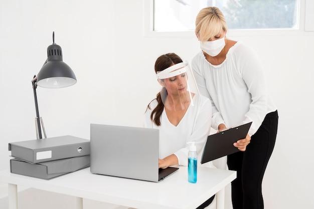 Donna che lavora in un ufficio e indossa la protezione per il viso vista frontale Foto Gratuite