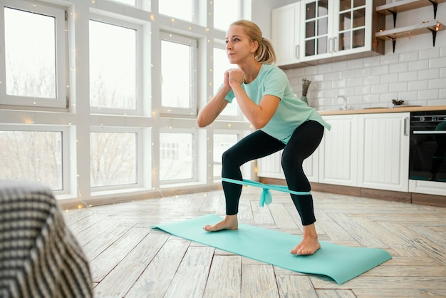Female working out on mat with elastic band Free Photo