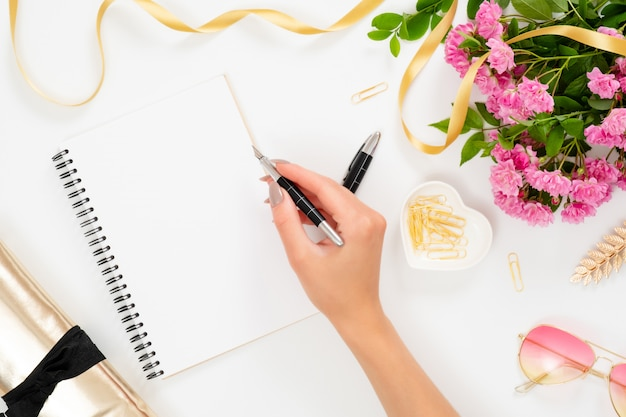 Female workspace with blank paper notebook and hand of woman holding pen, pink rose flowers, golden accessories, sunglasses Premium Photo