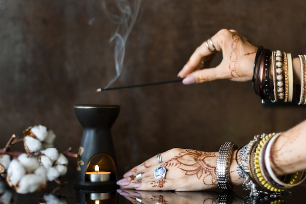 Female wrists painted with henna traditional indian oriental mehndi ornaments. hands dressed in metal bracelets and rings holding aromatic stick. aroma lamp and cotton flowers on background. Premium Photo