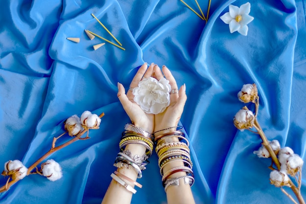 Female wrists painted with traditional indian oriental mehndi ornaments by henna. hands dressed in bracelets and rings hold white flower. blue fabric with folds and cotton branches on background. Premium Photo