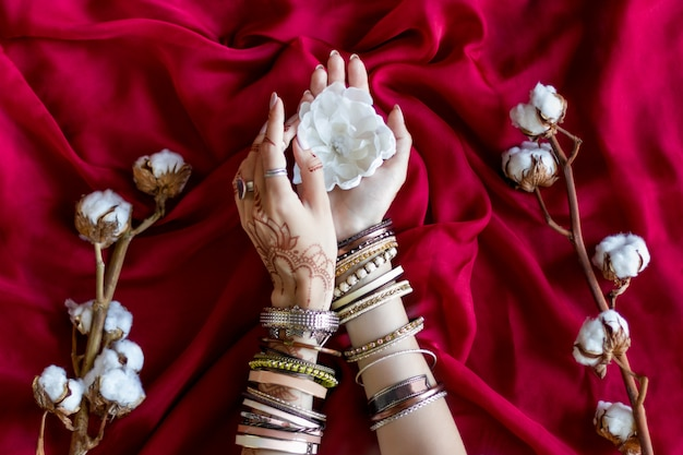 Female wrists painted with traditional indian oriental mehndi ornaments by henna. hands dressed in bracelets and rings hold white flower. vinous fabric with folds and cotton branches on background. Premium Photo