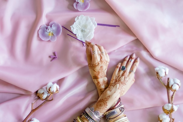 Female wrists painted with traditional indian oriental mehndi ornaments. hands dressed in bracelets and rings hold aroma stick. pink fabric with folds, cotton branches and candles on background. Premium Photo