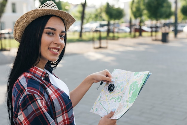 Female young traveler holding navigational compass and map while looking at camera Free Photo