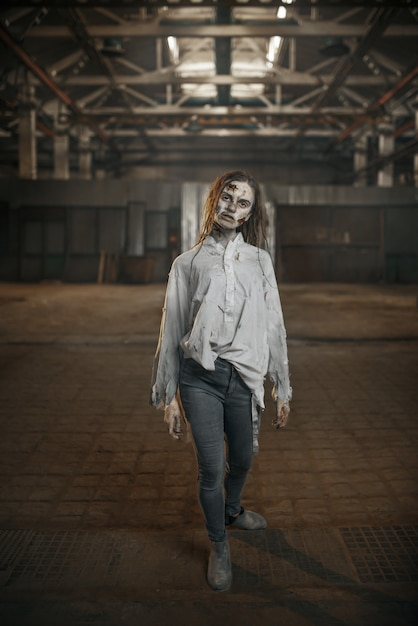 Female zombie walking in abandoned factory, horror Premium Photo