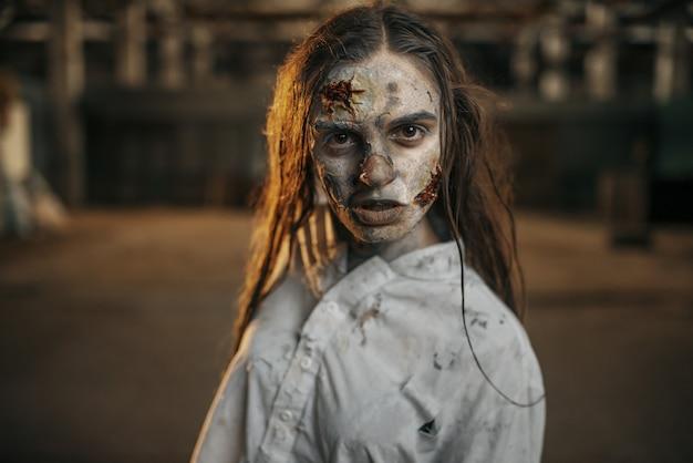 Female zombie walking in abandoned factory, horror Premium Photo