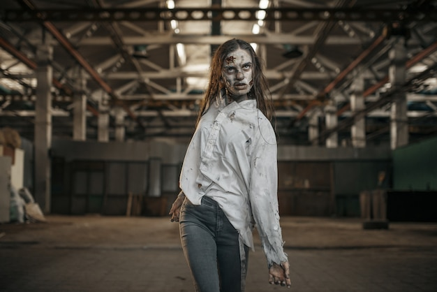 Female zombie walking in abandoned factory, scary place. horror in city, creepy crawlies attack, doomsday apocalypse, bloody evil monsters Premium Photo