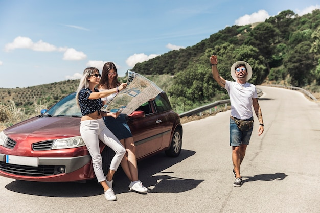 Females looking at map leaning on car while her male friend gesturing on road Free Photo