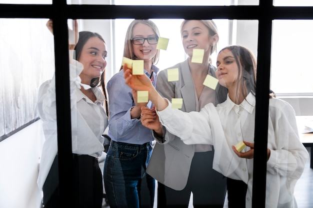 Females at office pasting sticky notes on window Free Photo