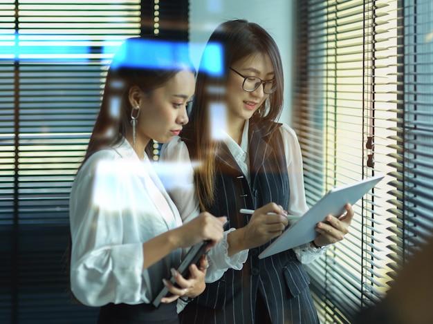 Офисные работники женского пола, консультирующие по своему проекту, стоя в офисе Premium Фотографии
