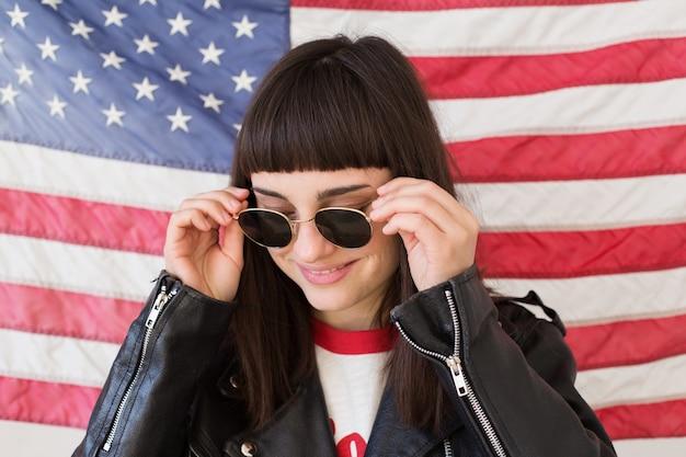 フェミニンな美しい女性または10代の少女は、アメリカの国旗、トレンディでファッショナブルなヒップスター、アメリカの愛国者の前で新しいサングラスのアイウェアを着用します 無料写真