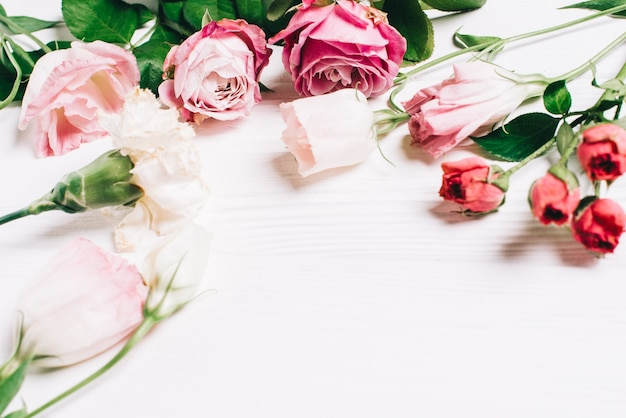 Feminine Desk Workspace Frame With Pink Roses And Petals On White Wooden Background Flat Lay