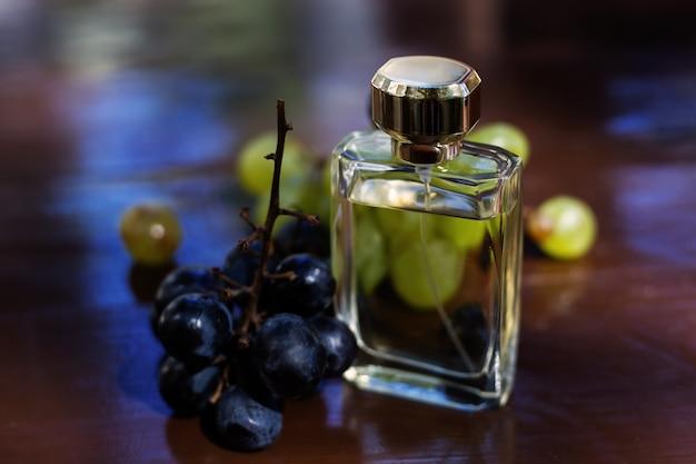 Женский стеклянный флакон духов с виноградом Premium Фотографии