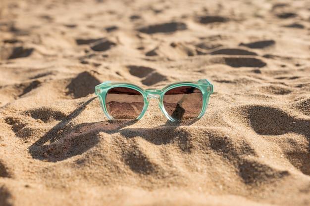 Feminine sunglasses on sand Free Photo