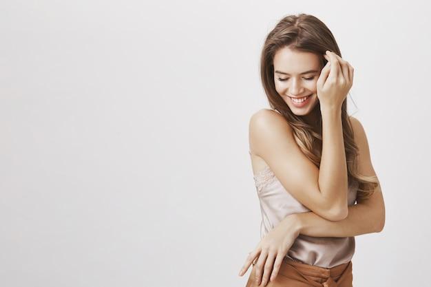 Женственная женщина смотрит вниз, улыбается и трогает волосы Бесплатные Фотографии