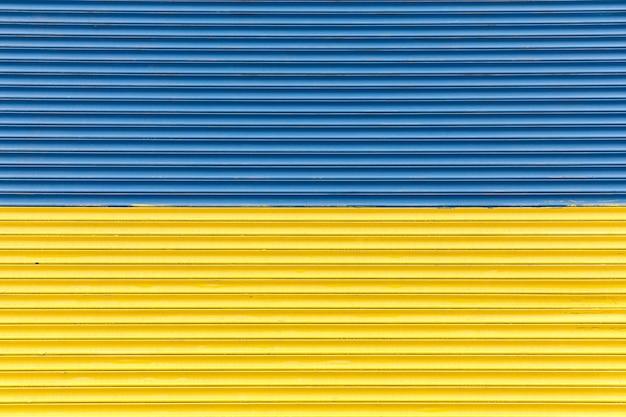 Забор окрашен в сине-желтые цвета украинского флага Premium Фотографии