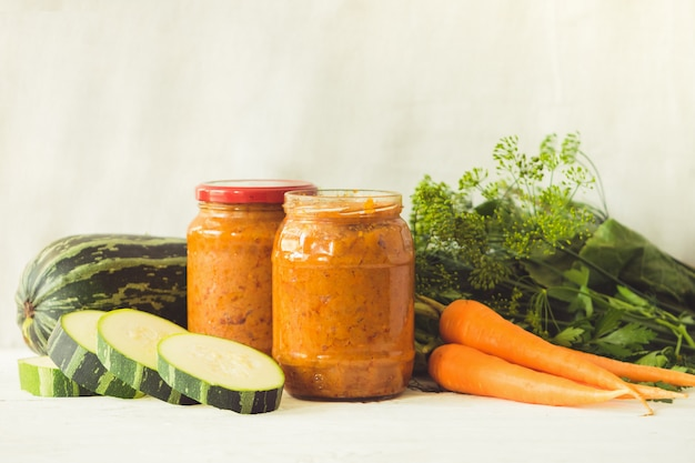 Fermented preserved canning various vegetables zucchini carrots in glass jars on table canned food. Premium Photo