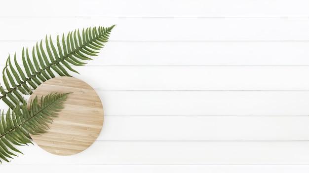 고 사리 잎과 하얀 나무 판넬 위에 원형 나무 접시. 무료 사진