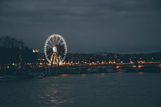 파리에서 밤 동안 흐린 하늘 아래 강과 건물로 둘러싸인 관람차 무료 사진