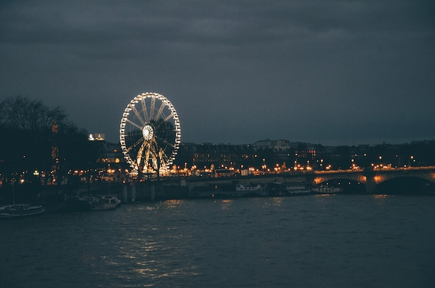 Ferris wheel surrounded by a river and buildings under a cloudy sky during the night in paris Free Photo