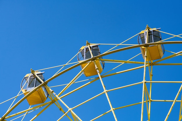 Ferris wheel with yellow cabins. gladness entertainment in city park. Premium Photo