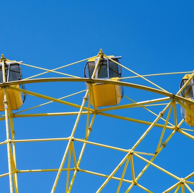 Ferris wheel with yellow cabins Premium Photo