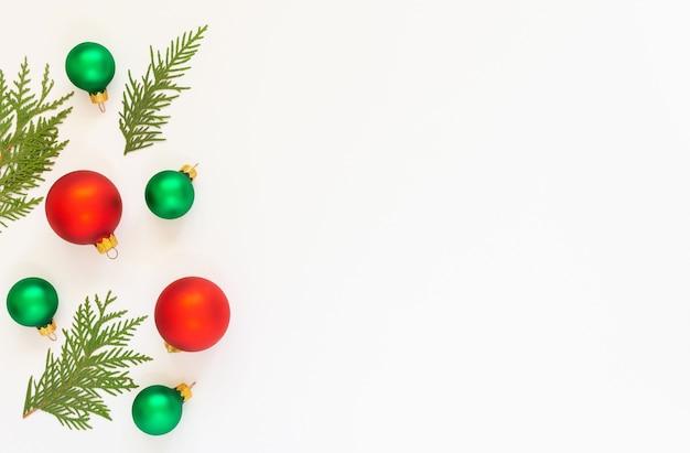 축제 배경, 흰색 배경에 전나무 나뭇 가지와 빨강 및 녹색 크리스마스 트리 볼, 평면 위치, 평면도, 복사 공간 프리미엄 사진