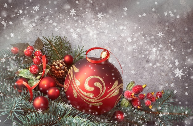 Festive background with christmas tree twigs decorated with red baubles and fir twigs Premium Photo