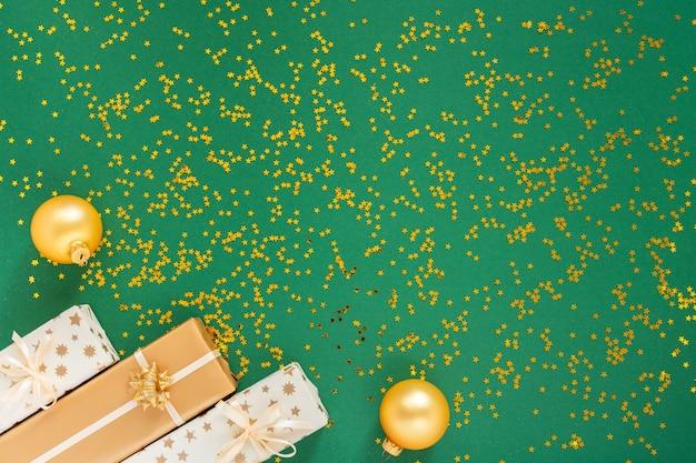 반짝이 골드 별과 녹색 배경에 장식, 선물 상자와 크리스마스 공 축제 배경 프리미엄 사진