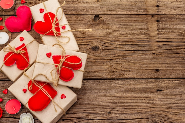 Festive boxes in craft paper with red felt hearts Premium Photo