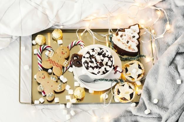 Праздничный завтрак в постель с горячим шоколадом, зефиром, мясным пирогом, пряничным человечком и сладостями. Premium Фотографии