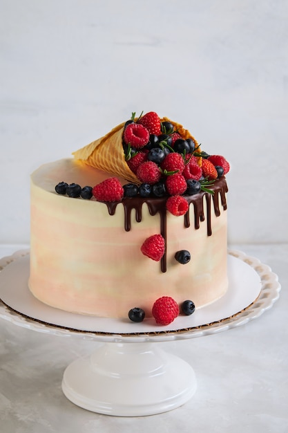 Festive cake with melting chocolate and assorted fruits in a waffle horn Premium Photo