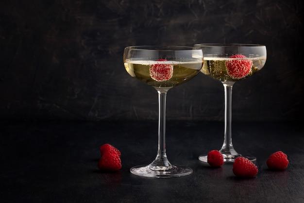 Festive champagne glasses with raspberries Premium Photo