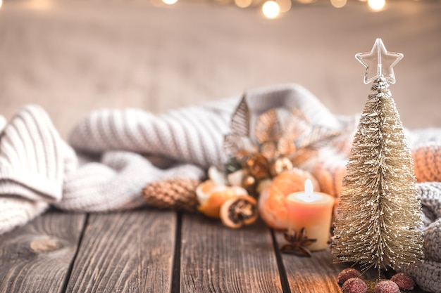Festive christmas cozy atmosphere with home decor and tangerines on a wooden background, home comfort concept Free Photo