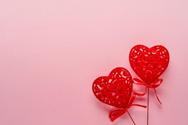 Праздничная композиция с двумя красными ажурными белыми сердечками на розовом фоне. вид сверху, копия пространства. концепция дня святого валентина. Premium Фотографии