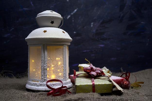 Праздничная концепция на рождество и новый год. красивая декоративная лампа светится на темном пространстве с подарочными коробками, барабанами и деревянной елкой. Premium Фотографии