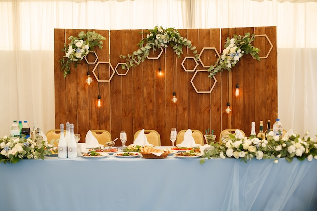 Festive decorated restaurant hall. place of celebration wedding or birthday party.  festive table with plates, glasses and dishes in the restaurant. Premium Photo