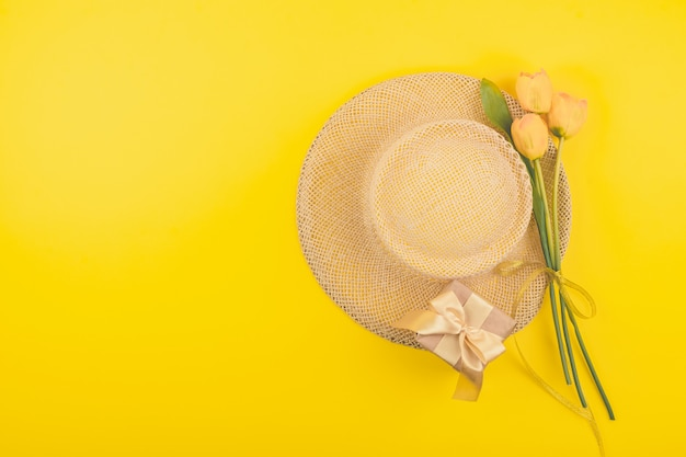 Festive female fashion flat lay with copy space. gift box, straw hat and yellow tulips Premium Photo