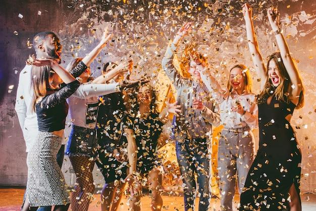 Festive friends in confetti together Free Photo