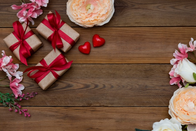 Festive gift boxes and bouquet of flowers on wooden background with copy space. valentine's day, love. Premium Photo