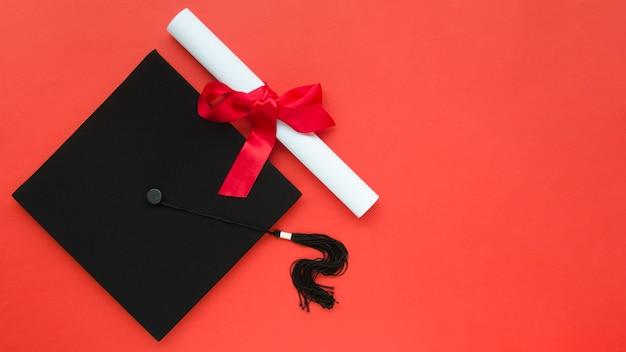 アカデミックキャップと卒業証書を備えたお祝いの卒業構成 Premium写真