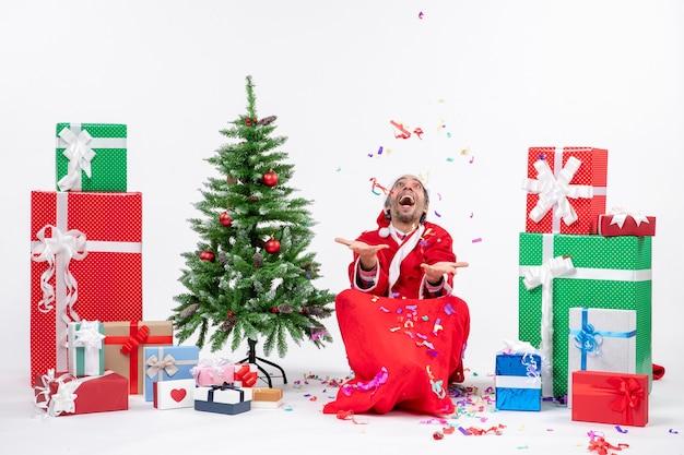 Праздничное праздничное настроение со счастливым санта-клаусом, сидящим на земле и играющим с рождественскими украшениями возле подарков и украшенной рождественской елкой на белом фоне Бесплатные Фотографии
