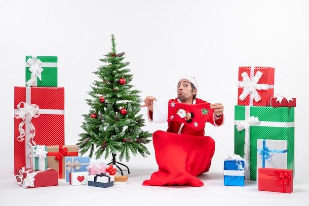 슬픈 산타 클로스가 바닥에 앉아 선물과 흰색 배경에 장식 된 크리스마스 트리 근처에 크리스마스 양말을 보여주는 축제 휴일 분위기 무료 사진