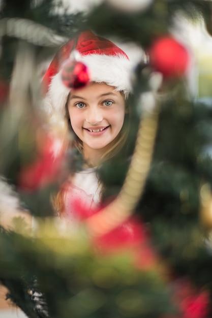 Festive litte girl decorating christmas tree Premium Photo