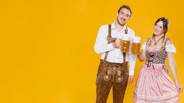 Праздничный мужчина и женщина с пивными кружками Premium Фотографии