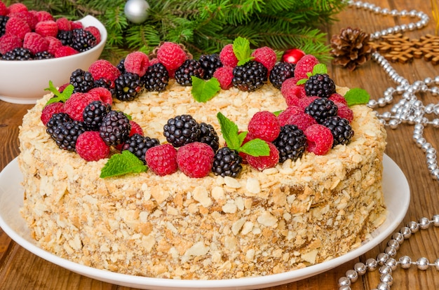 Festive napoleon cake with chocolate custard and berries on top for christmas and new year Premium Photo