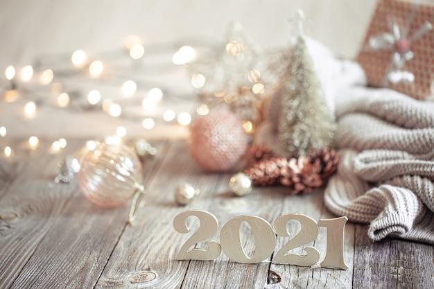 Composizione festiva del nuovo anno con il numero di legno del nuovo anno su uno sfondo sfocato chiaro con decorazioni natalizie. Foto Gratuite