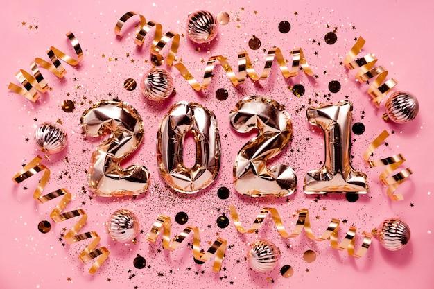 Праздничные новогодние шары из фольги из розового золота и рождественские украшения. горизонтальный вид сверху copyspace. Premium Фотографии