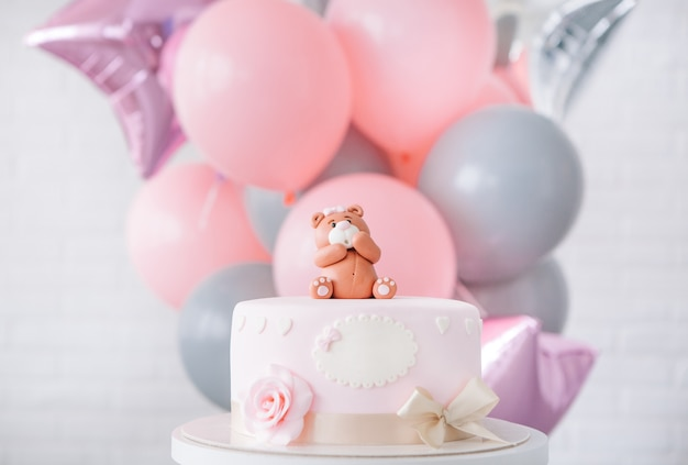 Festive pink cake with a bow and a bear on top of a background of balloons Free Photo